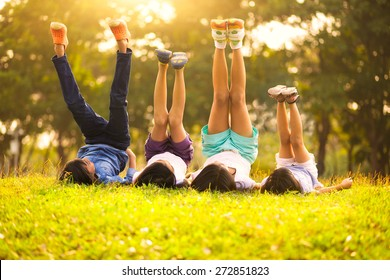 Group of happy children lying on green grass outdoors in spring park - Shutterstock ID 272851823