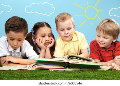Group of happy children lying on a green grass and reading books