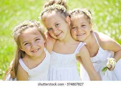 Group of happy children on green grass outdoors in spring park