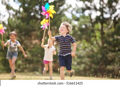 Group of happy children with pinwheels at the park