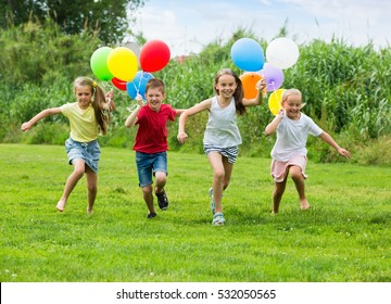 group of happy children playfully running with multicolored balloons on green meadow