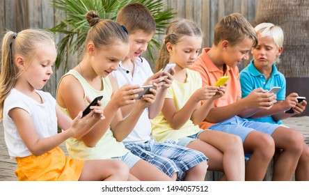 Group of happy children playing with mobile phones together outdoors