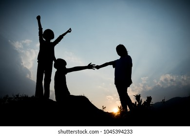 Group of happy children playing on hill at sunset, silhouette