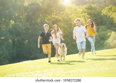 Group of happy children playing on green grass in a spring park with a dog. High quality photo.