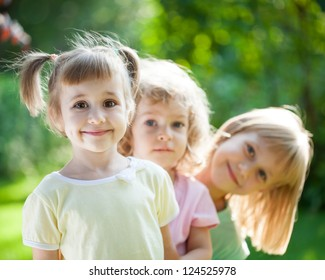 Group of happy children playing outdoors in spring park