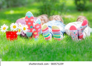 Group of happy children playing outdoors. Kids having fun in spring park. Friends lying on green grass