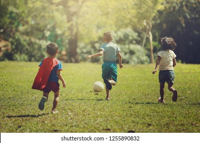 Group of happy children playing with soccer ball on meadow, together concept.