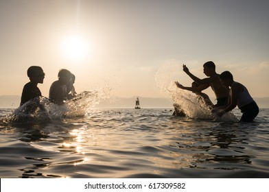Group of happy children playing and splashing in the sea beach. Kids having fun outdoors. Summer vacation and healthy lifestyle concept.