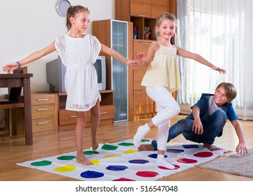Group of happy children playing at twister in house