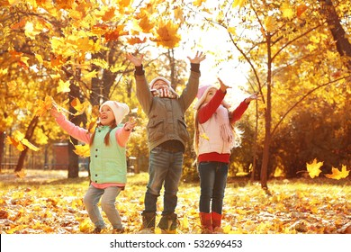 Group of happy children resting in beautiful autumn park