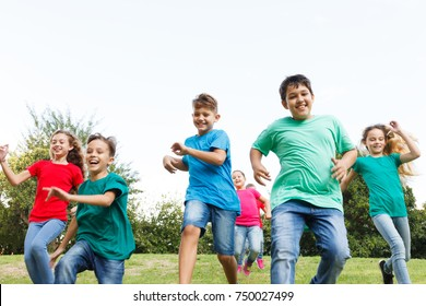 Group of happy children running outdoors.