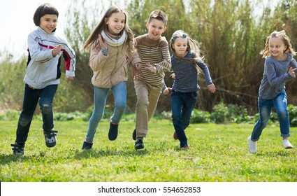 Group of happy children running in race and laughing outdoors