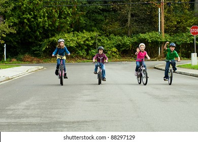 A group of happy children safely riding their bicycle on the street while wearing a helmet.