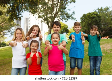 Group of happy children showing thumbs up