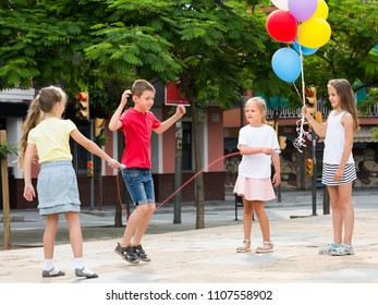 group of happy children skipping together with jumping rope on urban playground