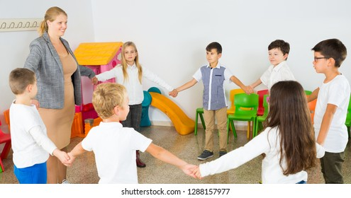 Group of happy children standing in circle holding hands, playing with their teacher in classroom during recess