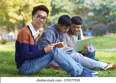 Group of Happy Chinese College Students  Reading Book on Lawn in Campus