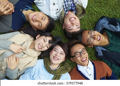Group of Happy Chinese College Students Lying on Lawn Lokking up to the Camera smile