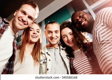 Group of happy college friends looking at camera