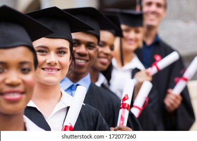 group of happy college graduates standing in a row