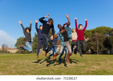 Group of Happy College Students Jumping at Park