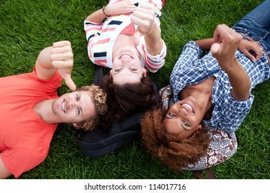 group of happy college students lying in the grass looking up
