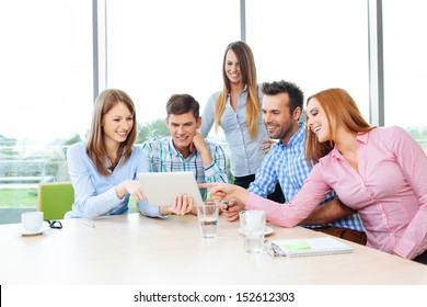 Group of happy corporate employees meeting in office sitting at the table
