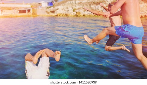 Group of happy crazy people having fun jumping in the sea water. Friends jump in mid air on sunny summer day on pool party at diving holiday. Travel vacation, friendship, youth holiday concept.
