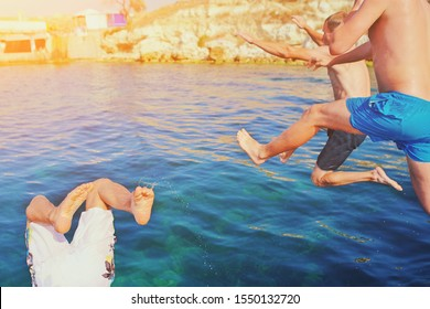 Group of happy crazy people having fun jumping in the sea water from boat. Friends jump in mid air on sunny day summer pool party at diving holiday. Travel vacation, friendship, youth holiday concept