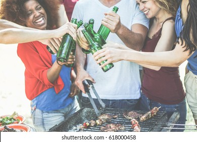 Group of happy diverse culture friends cheering with beer bottles at barbecue party - Young people having fun drinking nd eating together - Friendship concept - Main focus on front hands - Warm filter