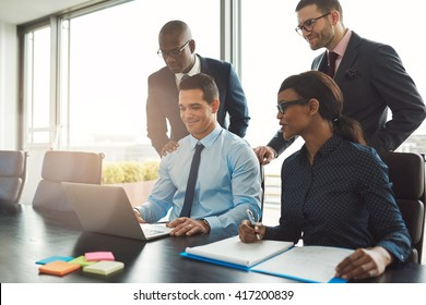 Group of happy diverse male and female business people in formal gathered around laptop computer in bright office
