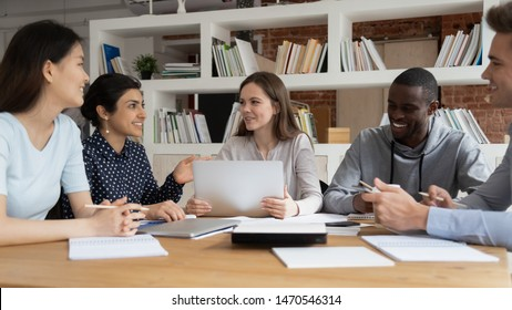 Group of happy diverse students sitting together at shared table in library, discussing school project together. Mixed race college friends preparing for exams or tests, collaborating in classroom.