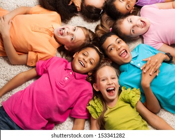 Group of happy diversity looking kids laying in star shape on the floor