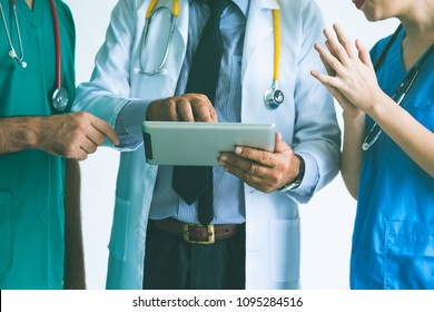 Group of happy doctor surgeon and nurse with tablet in meeting on white background, Healthcare and medical concept