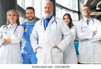 Group of happy doctors in hospital corridor, portrait.