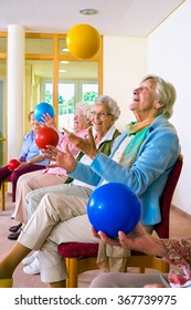 Group of happy elderly ladies in a seniors gym doing hand coordination exercises throwing and catching brightly colored plastic balls as they sit in their chairs