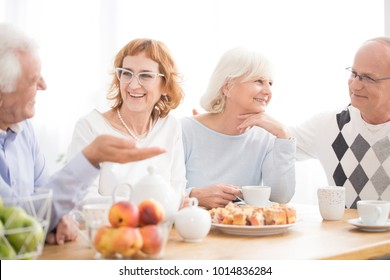 Group of happy elderly people spending lunch time together