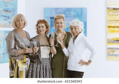 Group of happy elegant women spending time in museum