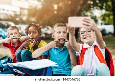 Group of happy elementary school students taking selfie. Primary education, friendship, childhood, and technology concept.