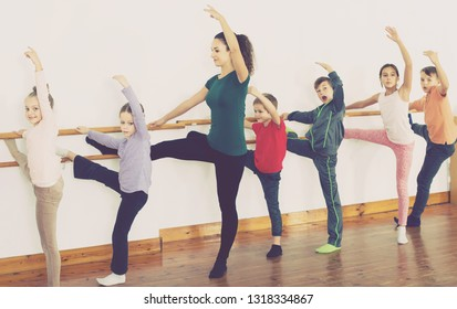 Group of happy european children practicing at the ballet barre