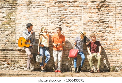 Group of happy excited friends having fun outdoor cheering with guitar - Young people enjoying spring summer time together at city town tour - Youth friendship concept on warm afternoon color filter