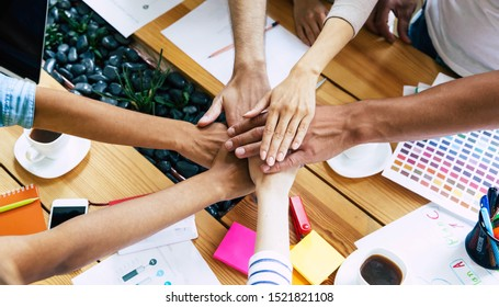 Group of happy, excited and successful modern people in office. Start up business team are holding hands together in circle. Company of young students are celebrating some win.
