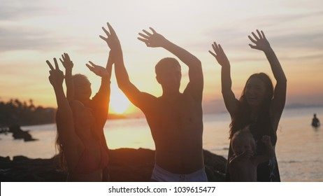 Group of happy family enjoying summer sunset rising their hands on a tropical beach