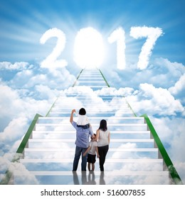group of happy family walks on the stairway and enters light door with cloud shaped number 2017