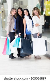 Group of happy female friends shopping and holding bags