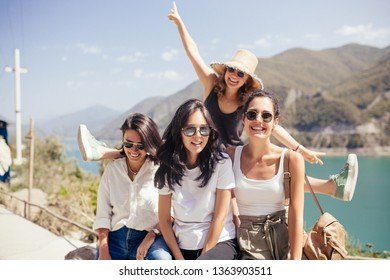 Group of happy female student girls having summer vacation in beautiful places with hills and mountains on summer day. Concept of active recreation and happy emotions. Friendship and communication