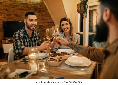 Group of happy friend toasting while having dinner at dining table.