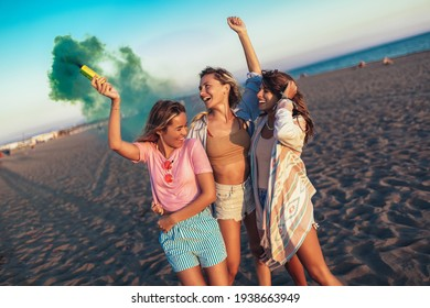 Group of happy friend walking on beautiful beach in summer sunset in their hands is smoke fontain