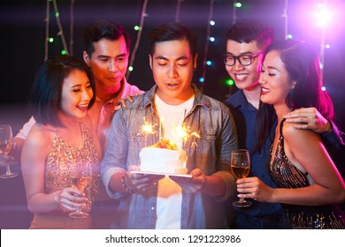 Group of happy friends at birthday party of young man in night club