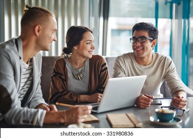 Group of happy friends or business people talking in office or cafe
